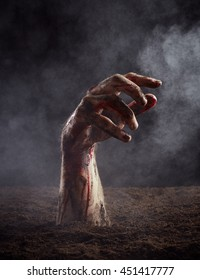 Zombie hand in blood and dirt climbs out of the ground