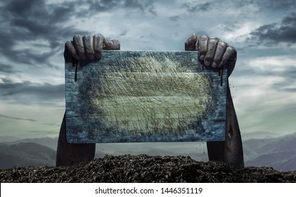 Zombie hand holding old wooden board, Empty space for text or draw