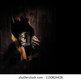 Zombie hand through hole cracked in rustic wood.Halloween theme.