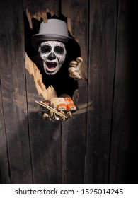 Zombie hand through hole cracked in rustic wood. Day of the dead theme.