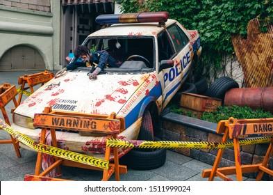 Zombie inside police car. Halloween decoration