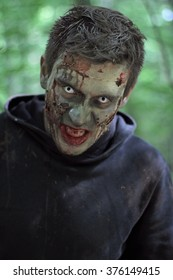 Zombie in a jacket with a hood in a forest.