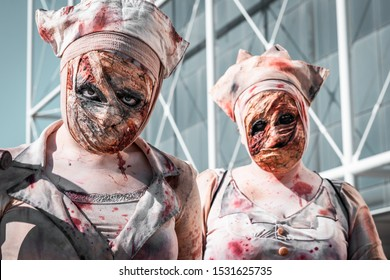 """Zombie nurses walking around with bloody outfits. Halloween costume design, horror and scary movies fans recreating the character from the popular tv show """"The walking dead"""". Bright sunny day, warm."""