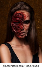 Zombie. A scary undead zombie girl. Girl on a gold background. Young woman in day of the dead mask skull face art. Halloween face art with fog on gold background
