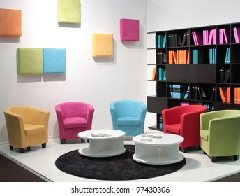 Zone for rest and work. It is a lot of armchairs of different color in an interior with a journal table
