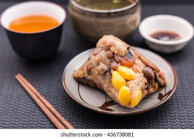 Zongzi or Asian Chinese sticky rice dumplings with Yellow tea, soup, sauce and chopsticks on dark table surface. Zongzi is a traditional Chinese food eaten during the dragon boat festival. / closeup