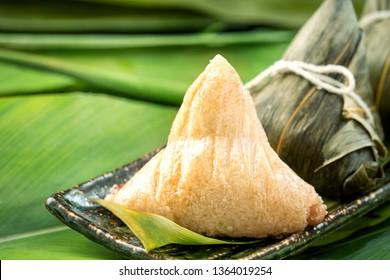 Zongzi - Close up, copy space, famous chinese food in dragon boat (duan wu) festival, steamed rice dumplings pyramidal shaped wrapped by bamboo leaves made by sticky rice raw ingredients