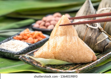 Zongzi - Close up, copy space, famous chinese tasty food in dragon boat (duan wu) festival, steamed rice dumplings pyramidal shaped wrapped by bamboo leaves made by sticky rice raw ingredients