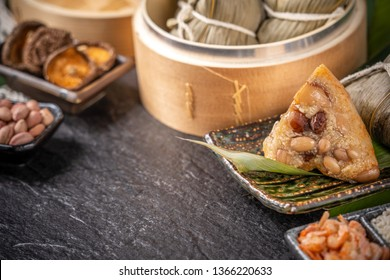 Zongzi - Close up, copy space, famous asian tasty handmade food in dragon boat(duan wu) festival, fresh from steamer steamed rice dumplings shaped pyramidal wrapped by leaves ingredients