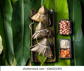 Zongzi - Close up, copy space, top view, famous asian chinese tasty handmade food in dragon boat(duan wu) festival, steamed rice dumplings shaped pyramidal by leaves ingredients
