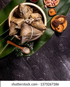 Zongzi - Close up, copy space, top view, flat lay. Famous asian chinese tasty handmade food in duan wu event, steamed rice dumplings shaped like pyramidal ingredient on black slate