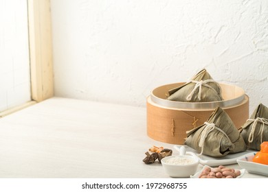 Zongzi. Rice dumpling for Chinese traditional Dragon Boat Festival (Duanwu Festival) on bright wooden table background with window.