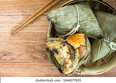 Zongzi or Traditional Chinese Sticky Rice Dumplings in a Bamboo basket on a Wooden Table