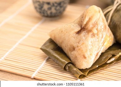 Zongzi - Traditional Dragon Boat Festival dumpling isolated on wood background.
