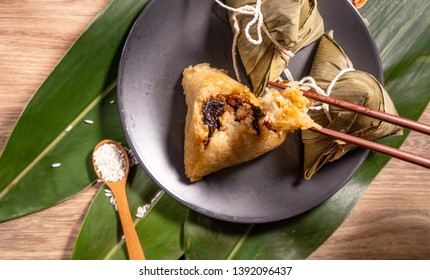 Zongzi, woman eating steamed rice dumplings on wooden table, food in dragon boat festival duanwu concept, close up, copy space, top view, flat lay