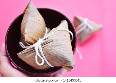 Zongzi in wooden bowl against red blurred one Zongzi background, Dragon Boat festival in China, traditional Chinese healthy food wrapped in bamboo leave and tie with rope homemade sticky rice dumpling