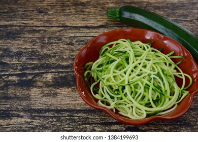 Zoodles (zucchini noodles) on wooden background. Negative space