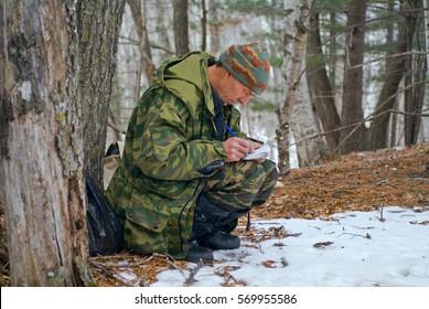 The zoologist explores an amur (Siberian) tiger in far-eastern taiga.
