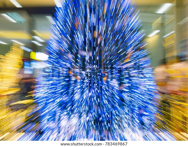 zoom burst  light blur image of  artificial pine christmas tree , bokeh of LED decorative light defocused background and textured,  for Christmas Eve , New Year party holiday and celebration