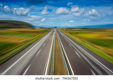 Zoom effect on empty modern highway going through fields