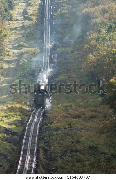 Zoom lens view of steam train at Mount Washington Cog Railway climbing up the summit