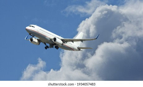 Zoom photo of Airbus A320 passenger airplane taking off reaching altitude above clouds in deep blue sky