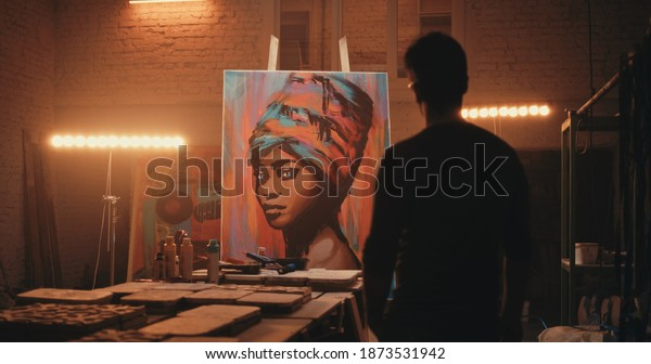 Zoom in view of anonymous man admiring colorful portrait of black woman while working in spacious illuminated studio