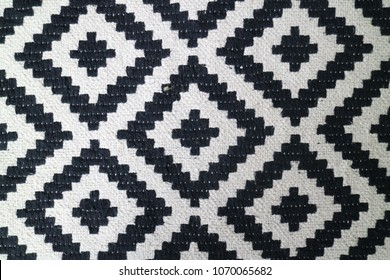 Zoomed close view of a black and white diamond geometric patterned rug. Detail of weave and pattern are visible, slight imperfections and debris visible.