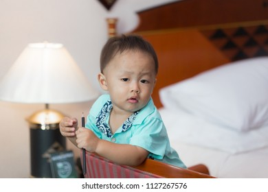 Zooming closeup facial portrait of a curious young lovely charming little Asian boy baby dresses in turquoise or soft blue shirt playing in a pencil on large wooden chair in decorative white bedroom