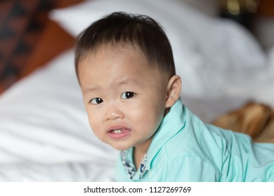 Zooming closeup facial portrait of a young lovely charming little Asian boy baby dresses in turquoise or soft blue shirt sitting crawling on a large bed while showing curiously smiling face to camera