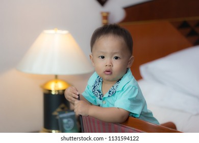 Zooming closeup facial portrait of a young lovely charming little Asian boy baby dresses in turquoise or soft blue shirt sitting on a large wooden chair while holding a pencil with lamp in background