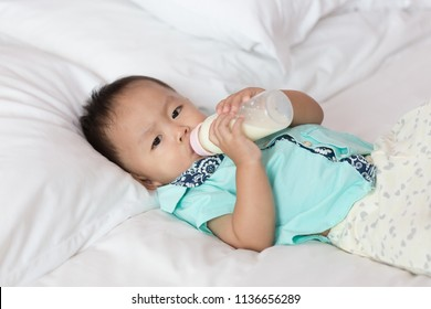 Zooming closeup facial portrait of a young lovely charming little Asian boy baby dresses in turquoise or soft blue shirt laying down on white bed while sleepy & drinking milk from bottle