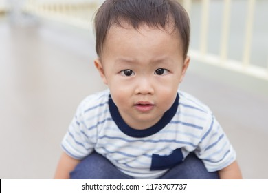 Zooming closeup facial portrait of a young lovely charming little Asian boy baby dresses in white & dark blue t-shirt sitting on his legs while frowning his brows