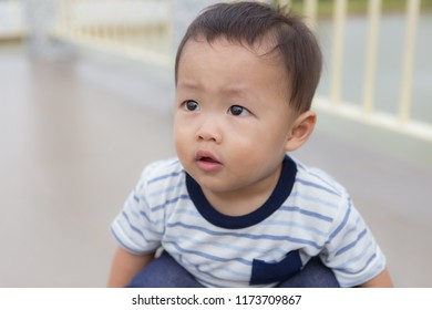 Zooming closeup facial portrait of a young lovely charming little Asian boy baby dresses in white & dark blue T-shirt sitting on his both legs glancing curiously on other way