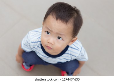 Zooming closeup facial portrait of a young lovely charming little Asian boy baby dresses in whitish and dark blue T-shirt sitting on his own legs while glancing in uprisen angle to the other site