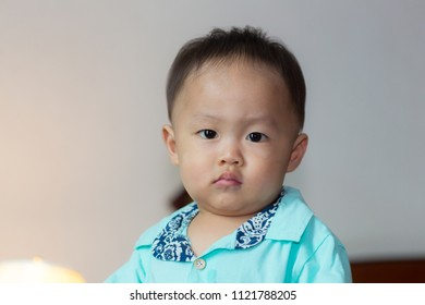 Zooming closeup facial view of a young lovely charming little Asian boy baby dressed in turquoise or soft blue shirt sitting while frowning his brows looking to the camera