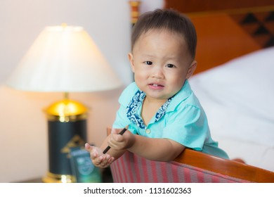 Zooming closeup facial view of a young lovely charming little Asian boy baby dresses in turquoise or soft blue shirt sitting on large wooden chair playing a pencil while smiling happily