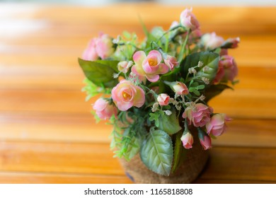 Zooming closeup macro view of beautiful charming artificial flowers in a little vase on blurry brownish wooden table