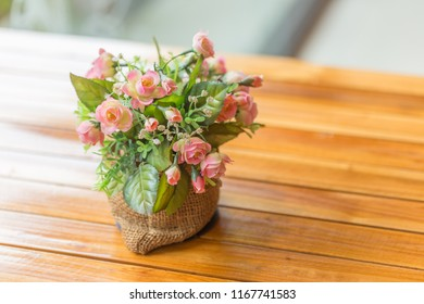 Zooming closeup macro view of little beautiful fragrance flowers in classic vase on brownish wooden table in an environmental atmospheric restaurant
