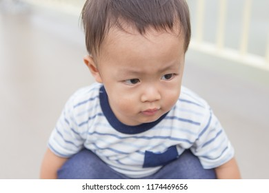 Zooming closeup macro view of a young lovely charming little Asian boy baby dresses in whitish and dark blue T-shirt sitting on his own legs while glancing at the other point