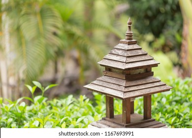 Zooming closeup outdoor view of charming little brownish wooden artificial shrine with fluorescent lamp inside in an environmental atmospheric garden