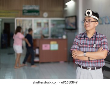 Zooming closeup portrait frontal view of a young nice looking Asian male doctor standing happily with his stethoscope, spectacles, vintage surgical headlight in front of a counter inside a clinic.