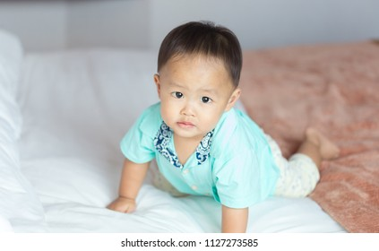 Zooming closeup portrait of a young lovely charming little Asian boy baby dresses in turquoise or soft blue shirt crawling on a large bed while looking at the camera in a white decorative bedroom
