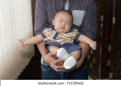 Zooming closeup view of charming & lovely sleeping Asian baby boy in a warming hold of his own guardian in a living room nearby whitish curtains and brownish wooden blinder as a blurred background