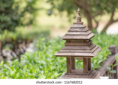 Zooming closeup view of old lovely charming little brownish wooden shrine with its fluorescent lamp below in an atmospheric environmental garden