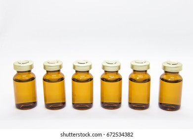 Zooming closeup view of six small yellowish translucent bottles of watery drug for intravenous , intradermal or intramuscular injections for patients in a hospital , clinic or medical center