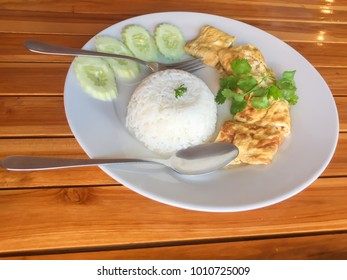 zooming closeup view of Thai style delicious minced shrimp in omelette serves with warm steamed rice , sliced cucumbers and coriander on large rounded whitish dish on reflective brownish wooden table