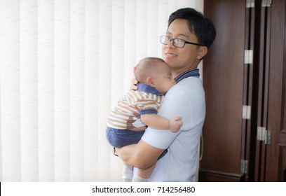 Zooming closeup view of a young handsome Asian male wearing eyeglasses carrying his lovely little sleeping boy baby with warmth and love by a whitish closing curtains and brownish wooden blinder