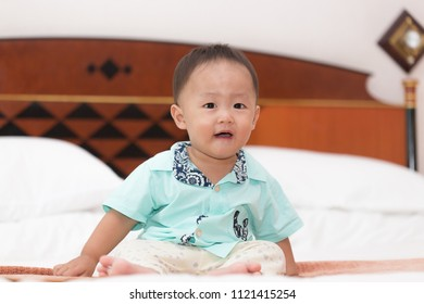 Zooming closeup view of a young lovely charming little Asian boy baby dresses in turquoise or soft blue shirt sitting while smiling happily on large bed in in a huge decorative bedroom