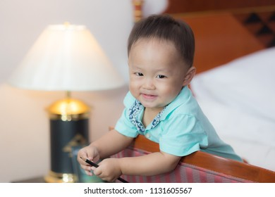 Zooming closeup view of a young lovely charming little Asian boy baby dresses in turquoise or soft blue shirt sitting on large wooden chair holding a pencil while smiling happily inside a bedroom